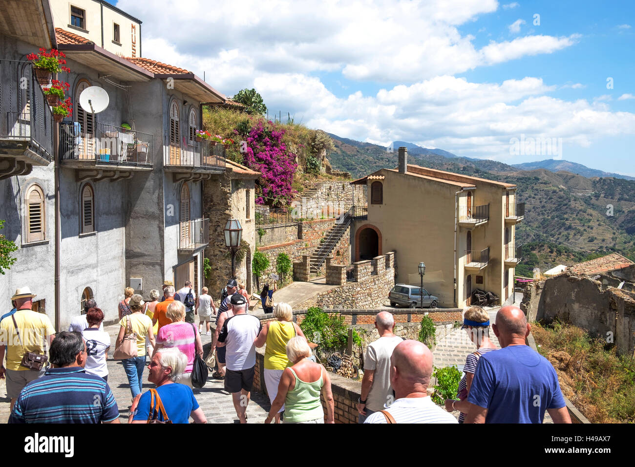 A tourist group on a visit to the mountain village of Savoca on the island of Sicily, Italy. - Stock Image