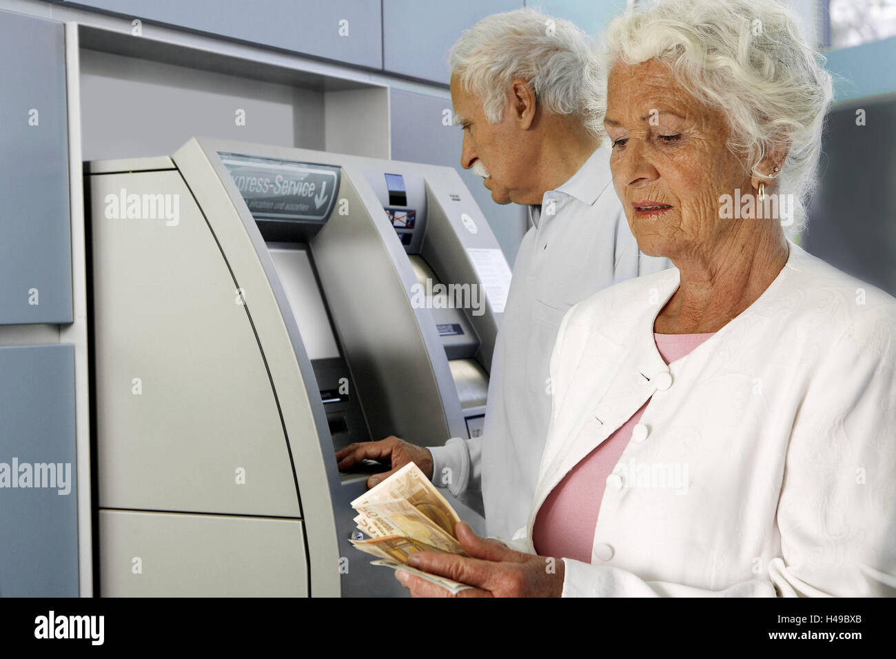 Senior couple, bancomat, cash, take off, people, senior citizens, couple, white haired, bank, financial institution, - Stock Image