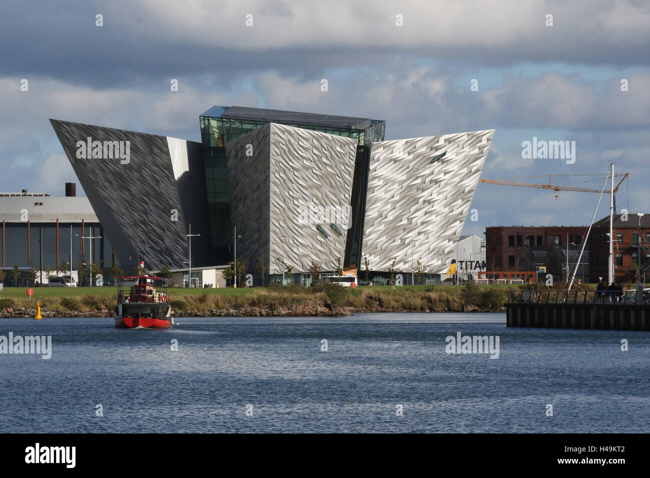 "The Titanic Building  in Belfast's Titanic Quarter.In the foreground is the ""Mona"", a boat used for Titanic Boat Stock Photo"
