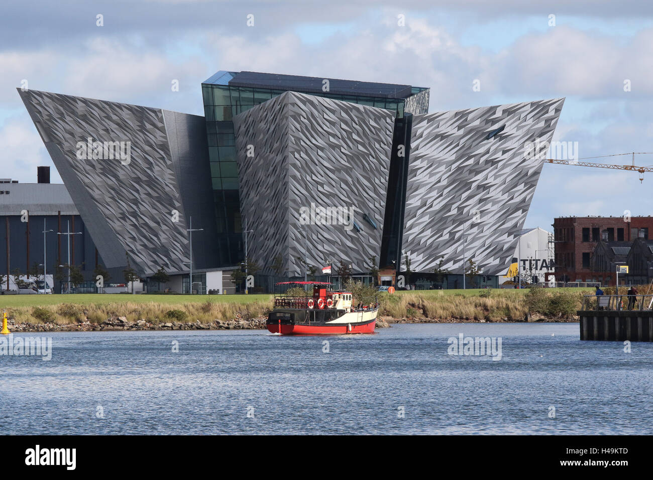 """The Titanic Building  in Belfast's Titanic Quarter.In the foreground is the """"Mona"""", a boat used for Titanic Boat Stock Photo"""