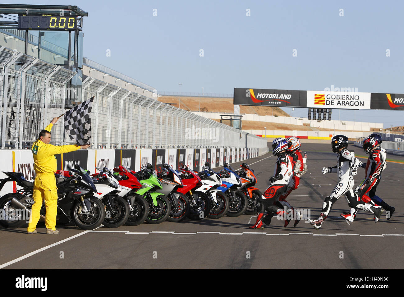 Motorcycle 1000cc comparison test, engine country Aragon Spain, supersportsman, drivers running to the motorcycles, - Stock Image