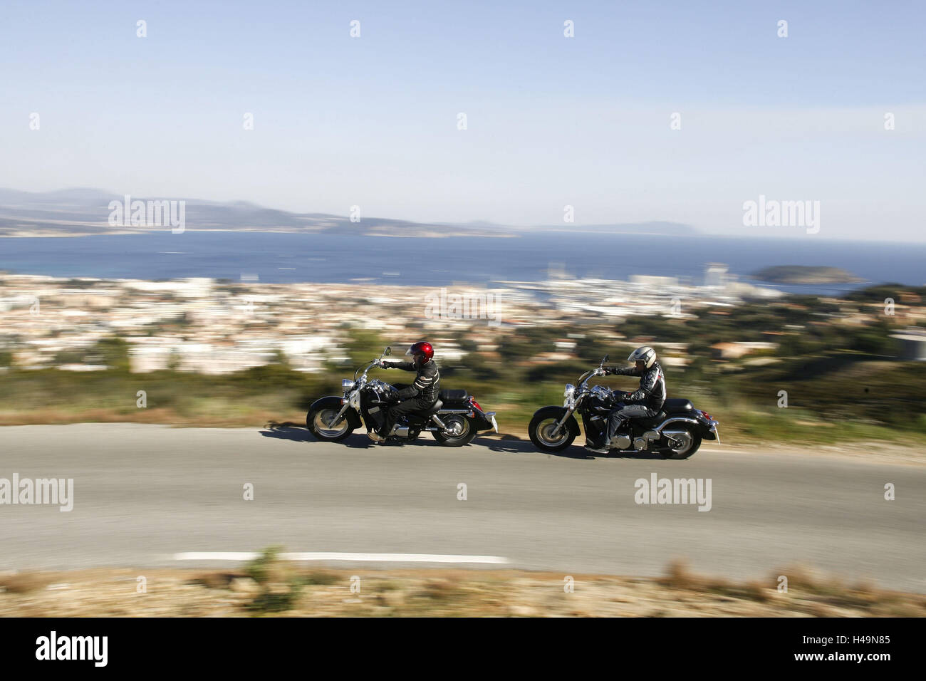 two motorcyclists, cruisers, country road, South of France, Mediterranean landscape, one after the other, - Stock Image