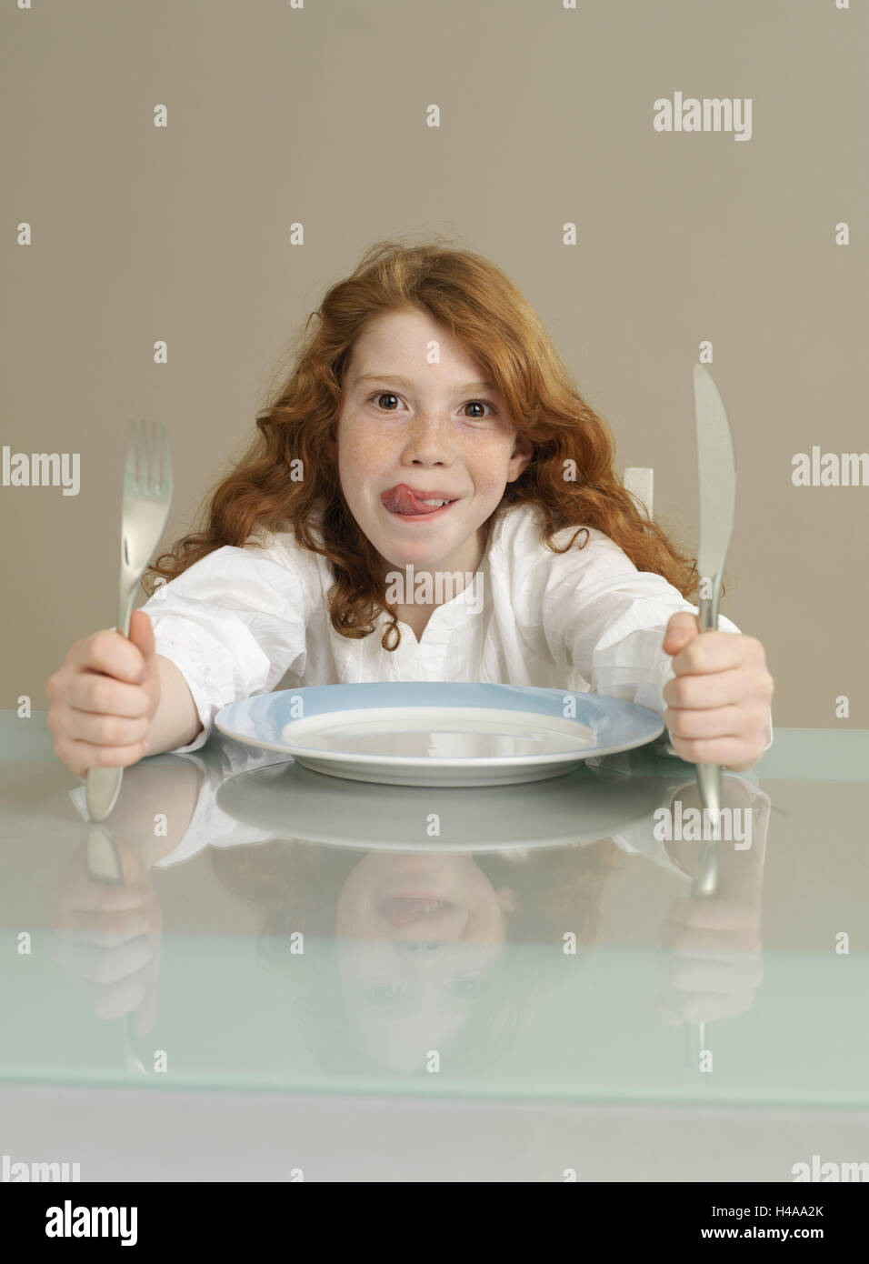 Table, girl, red-haired, cutlery, facial play, tongue, lips, leak, hungry, wait, portrait, dining table, cover, - Stock Image