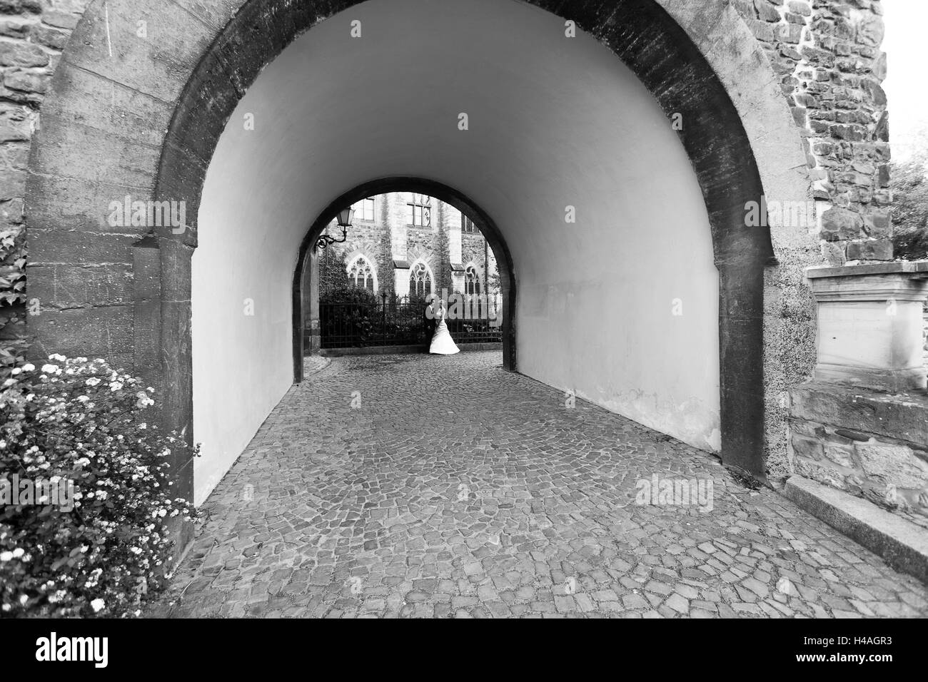 Bride and groom in ecclesiastical round arch, b/w - Stock Image