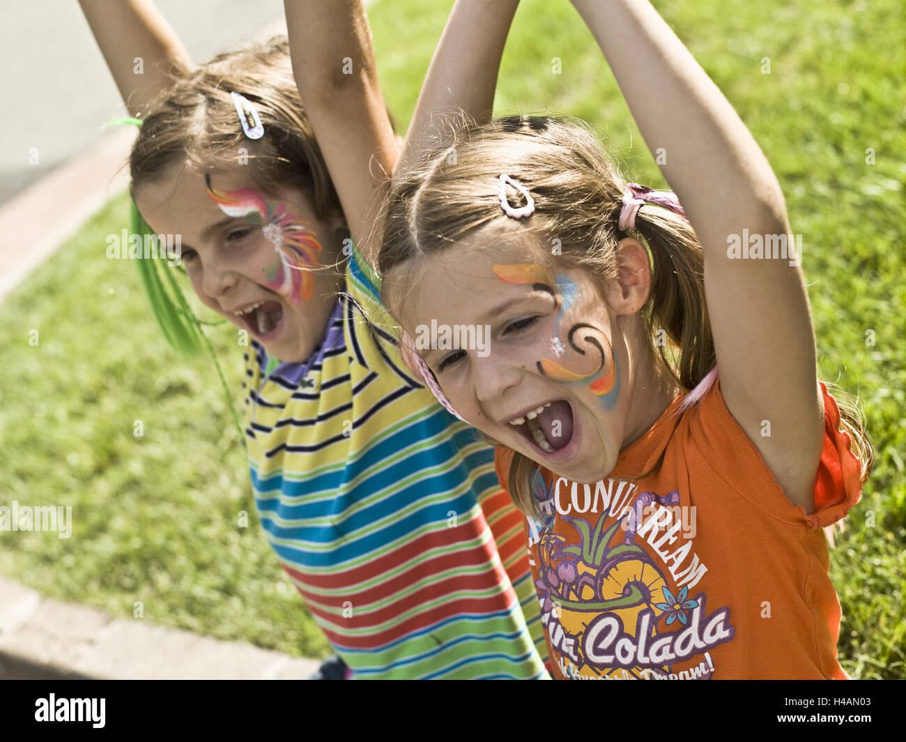 Girls, twins, painted faces, laugh, gesture, rejoice, portrait, summer, - Stock Image