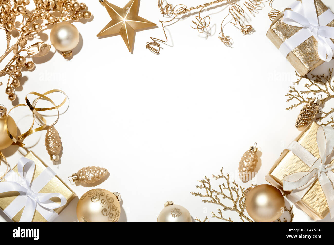 Golden Christmas decorations on white background - Stock Image