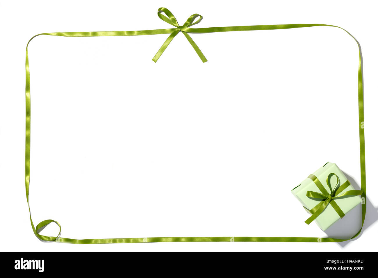 Green ribbon and gift box on white background - Stock Image