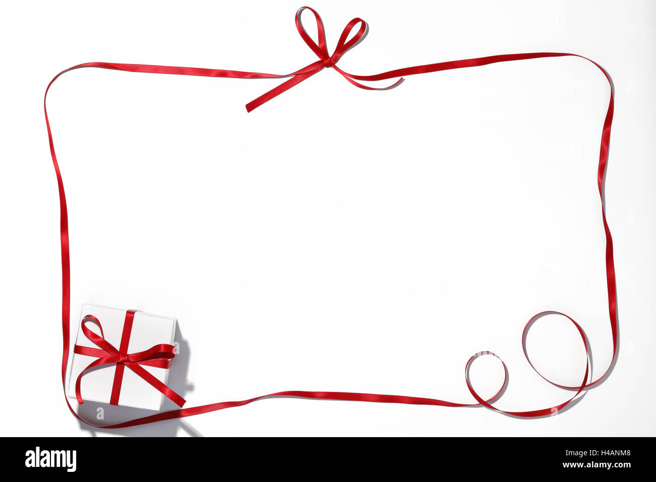 Red ribbon and gift box on white background - Stock Image