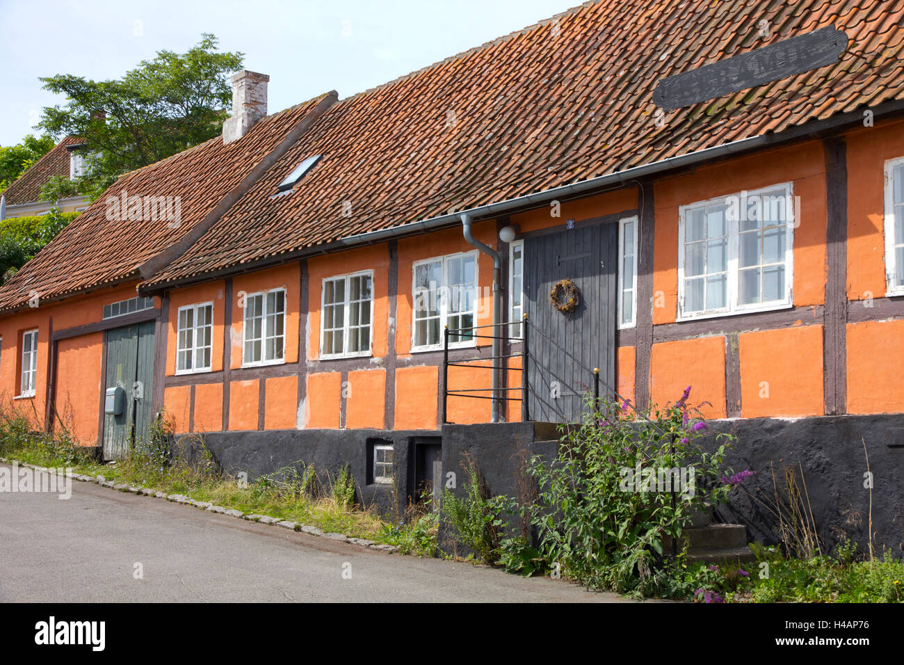 Colorful tiled roof shops and houses characterize the coastal village of Svaneke on the Danish island of Bornholm. Stock Photo