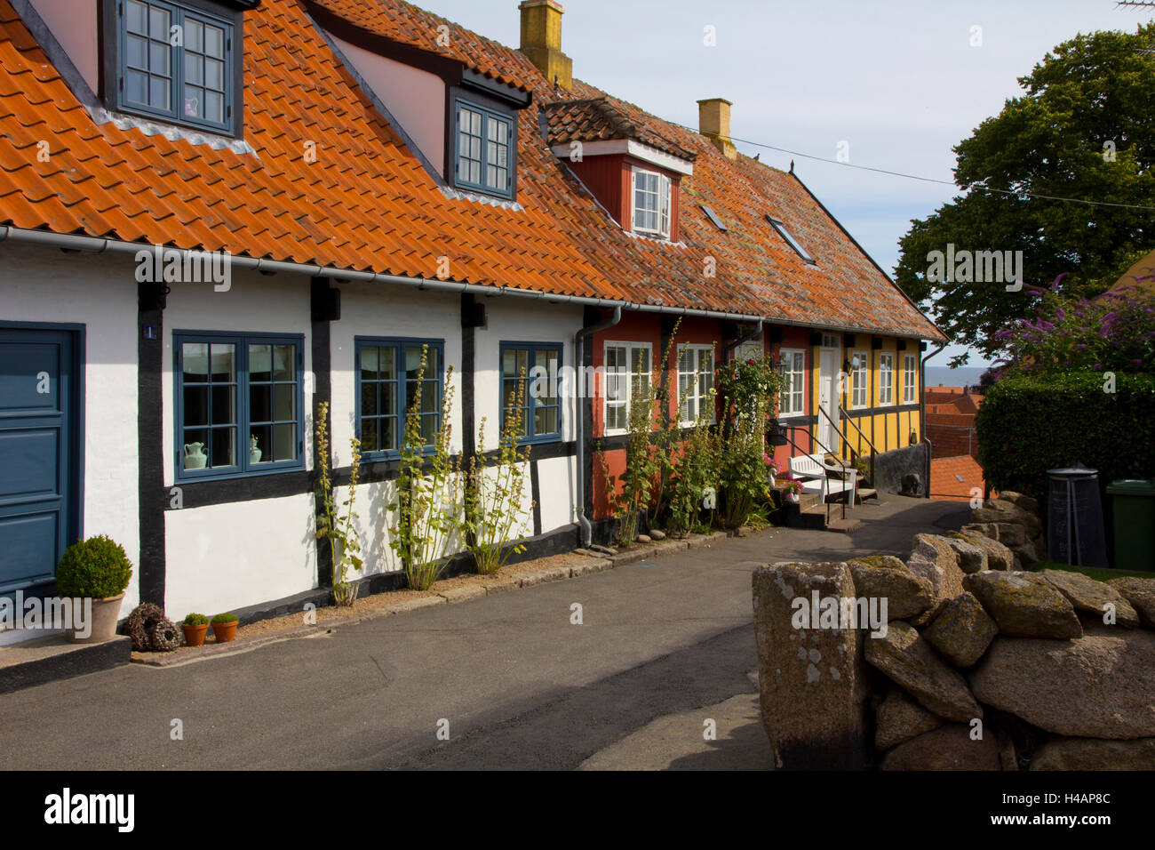Colorful tiled-roof shops and houses characterize the coastal village of Svaneke on the Danish island of Bornholm. Stock Photo