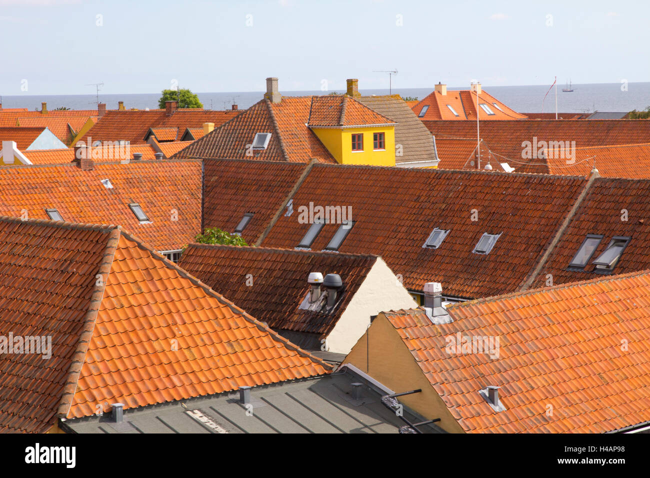 Colorful tiled-roof houses and shops characterize the coastal village of Svaneke on the Danish island of Bornholm. Stock Photo