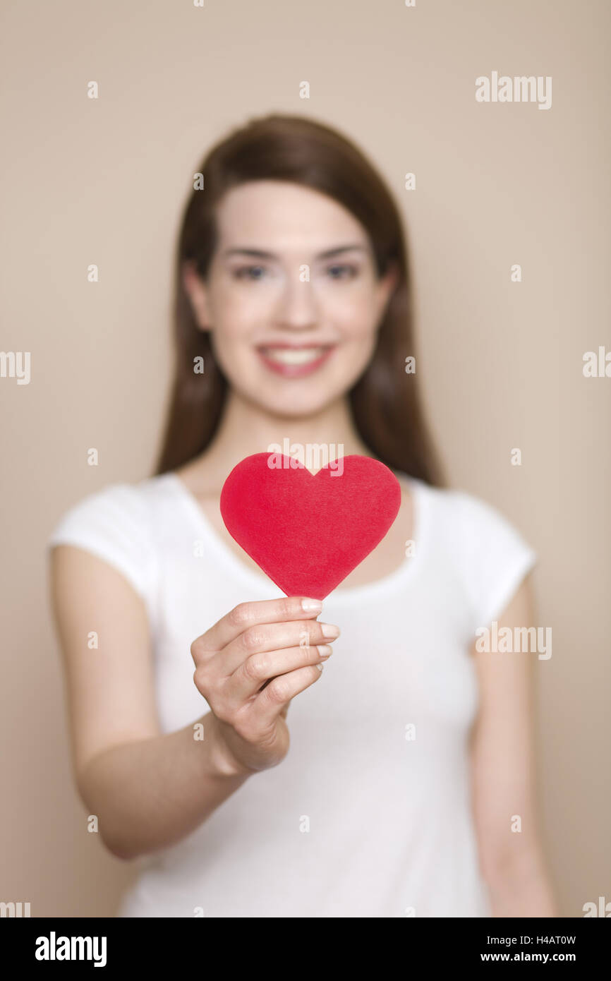 Woman holds red heart in her hand, happ, smile, portrait, low depth of field, - Stock Image