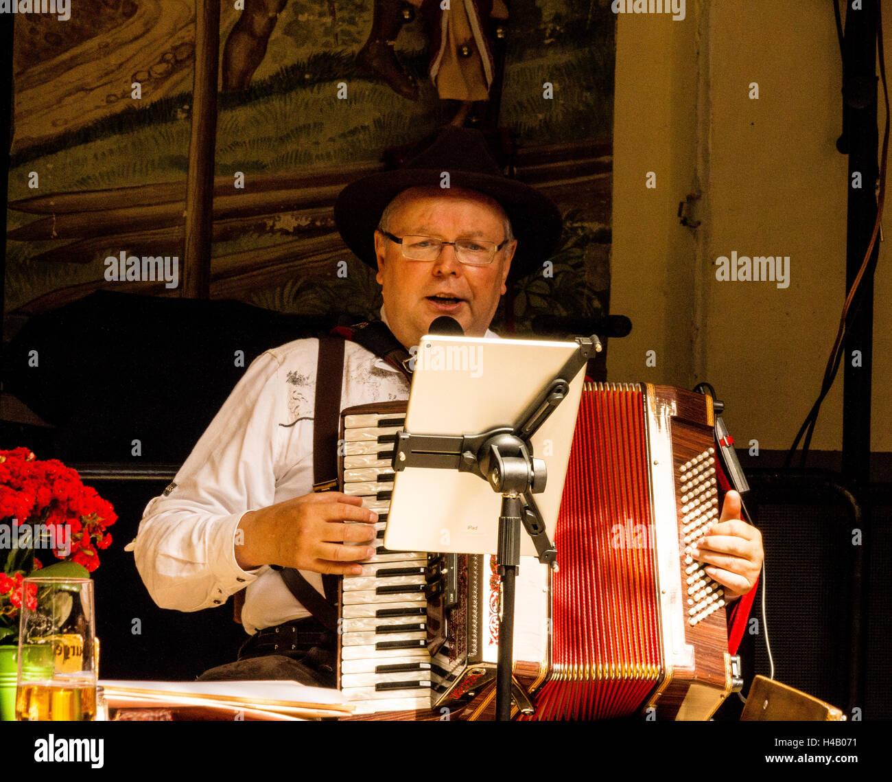 Accordion player wearing traditional Bavarian  costume, Rudesheim, Rhine Gorge, Germany, Europe - Stock Image