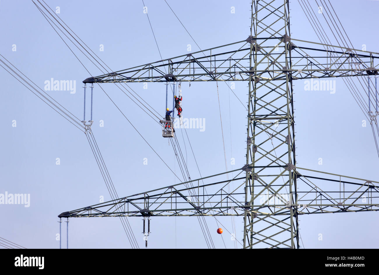 High-voltage pole, power line wire installation, man climbing to ...