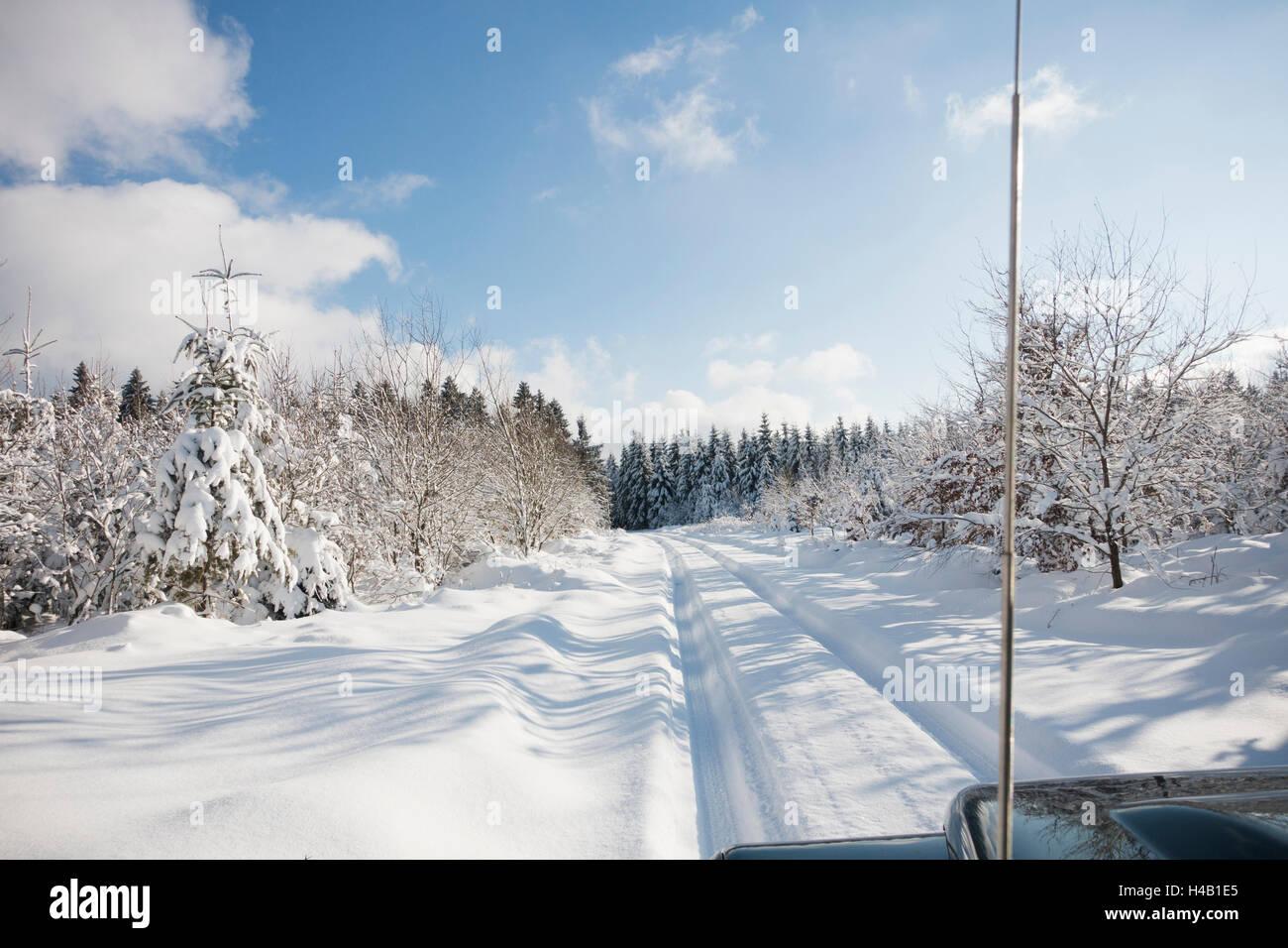 Tyre tracks in deep snow in winter scenery - Stock Image