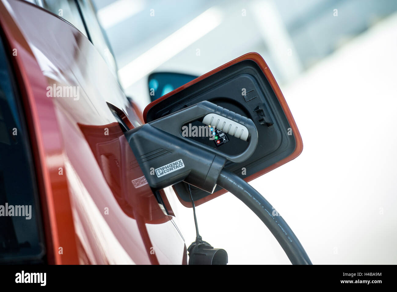 Electric car is being charged at a charging station - Stock Image