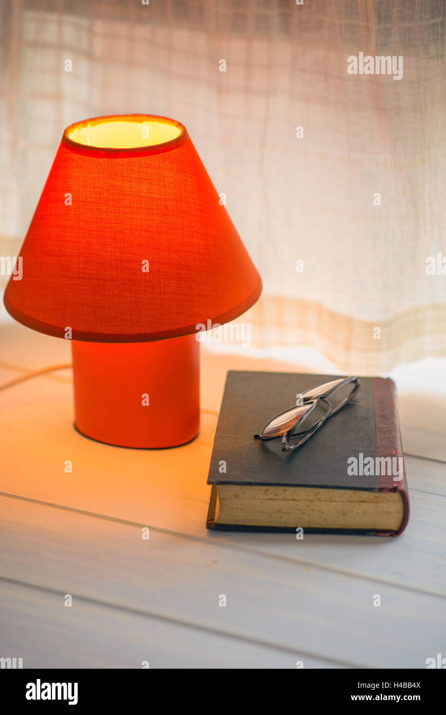 red desk lamp, book and glasses on window sill. copy space - Stock Image
