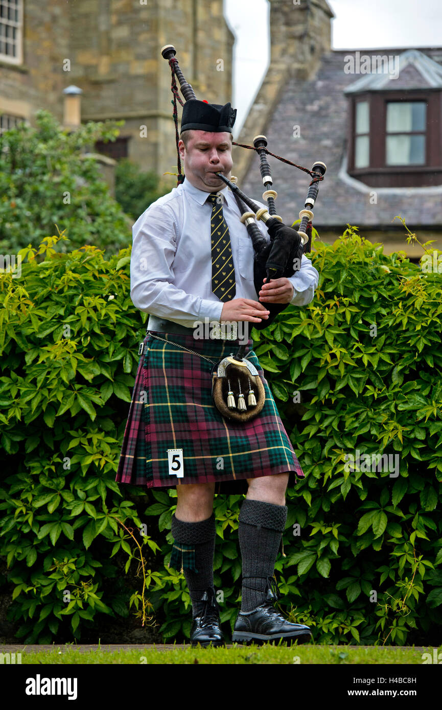 Solo bagpiper playing bagpipes in kilt, Bagpiper Music Competition, Ceres Highland Games, Ceres, Scotland, United - Stock Image