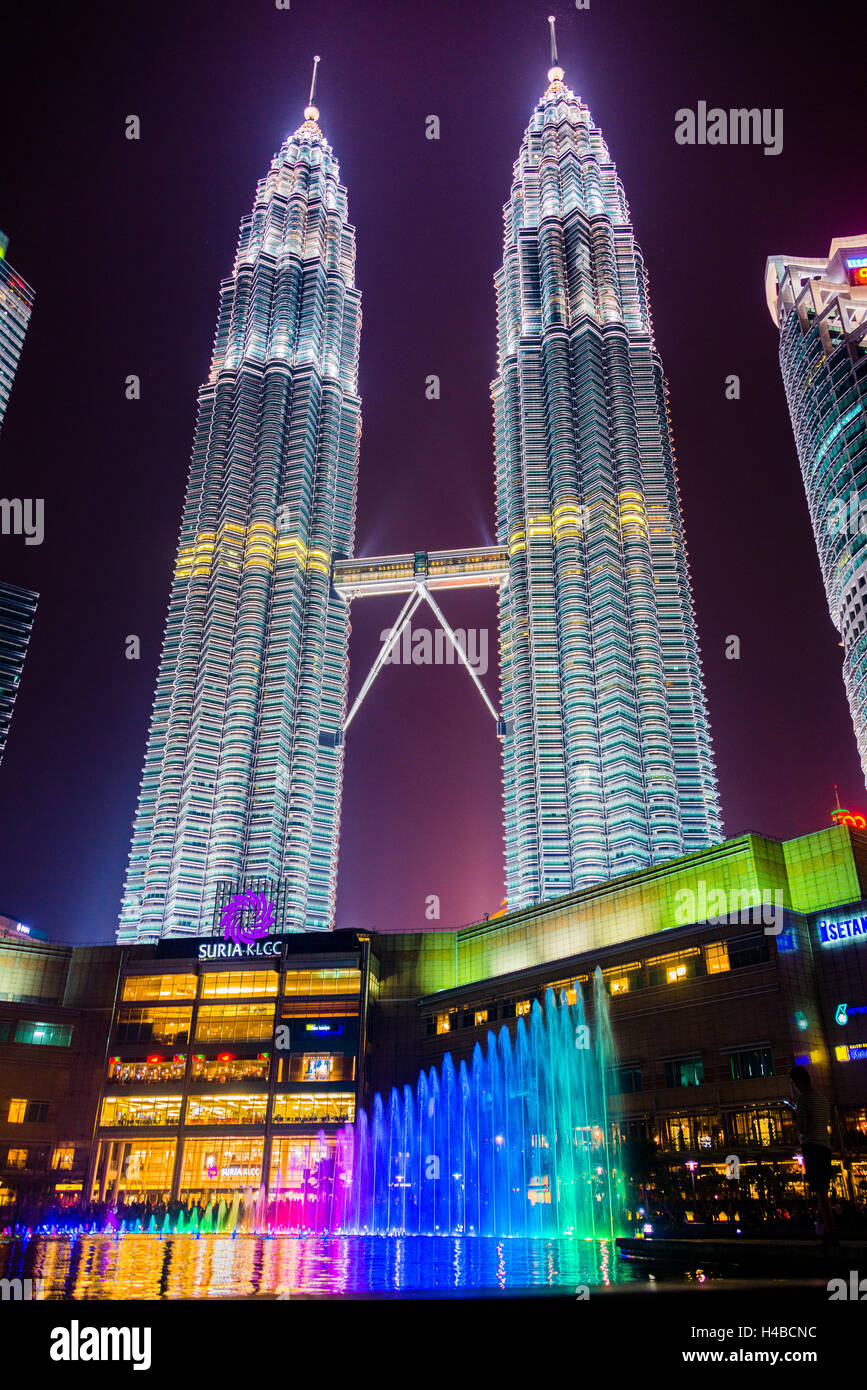 Lighted Petronas Towers with multicolored fountain at night, Kuala Lumpur, Malaysia - Stock Image