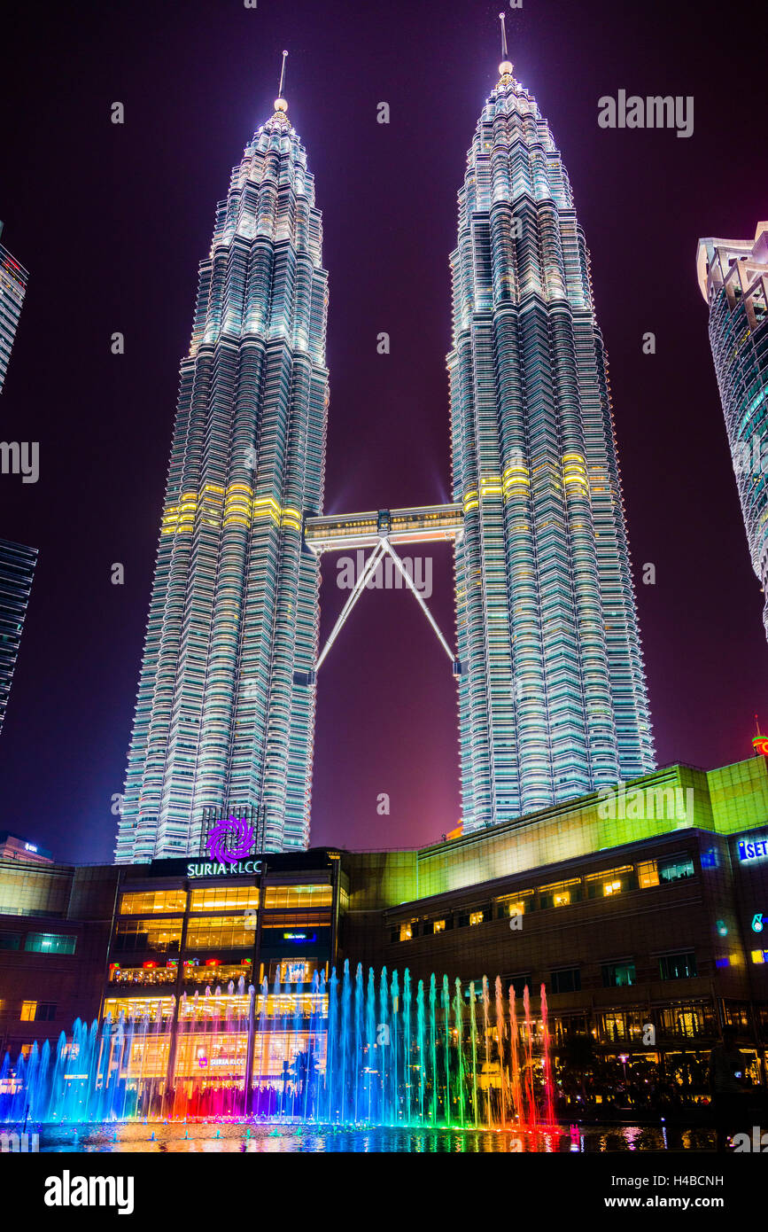 Lighted Petronas Towers with colored fountain at night, Kuala Lumpur, Malaysia - Stock Image