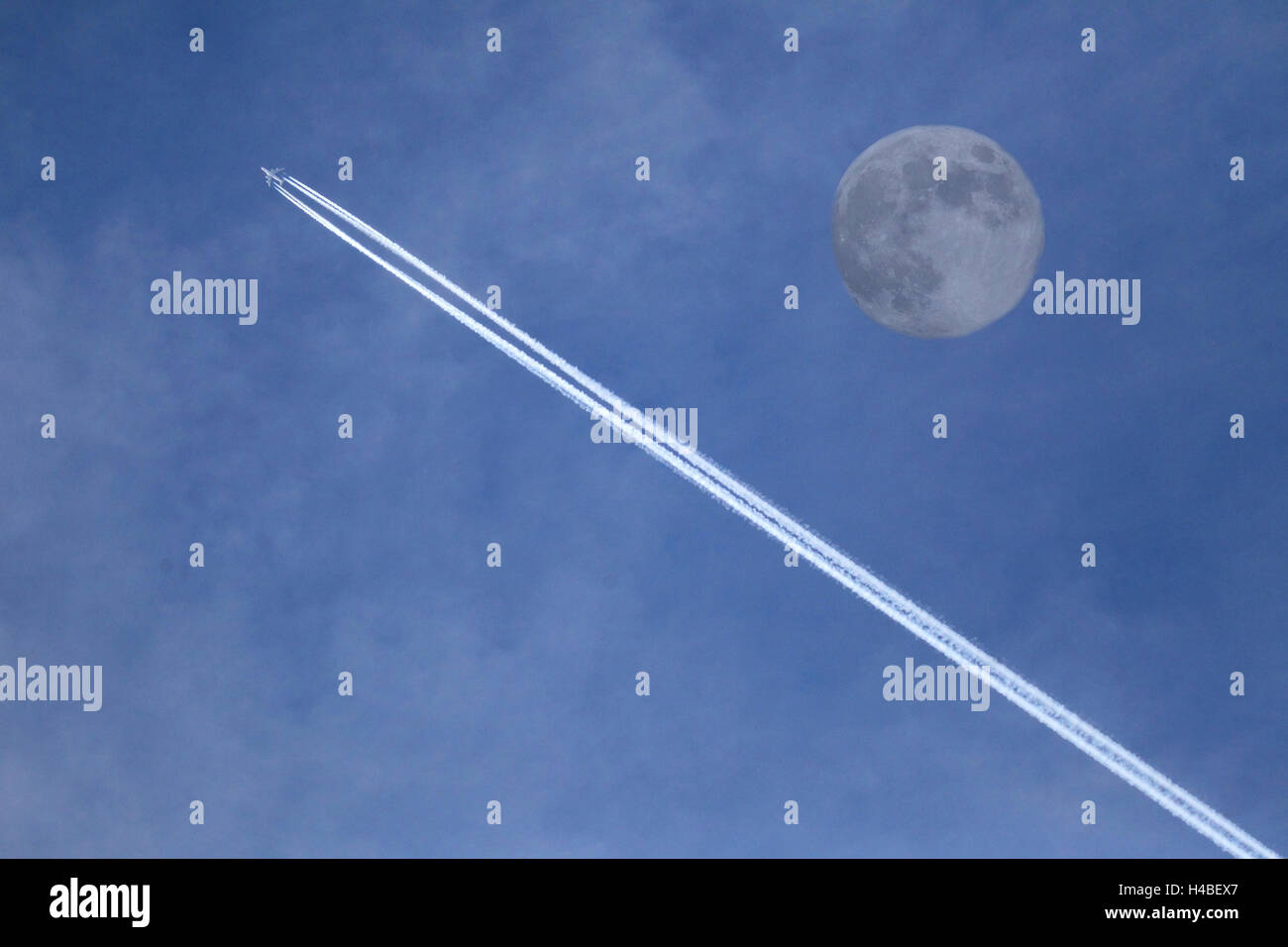 Jet plane with condensation strips and moon [M] - Stock Image