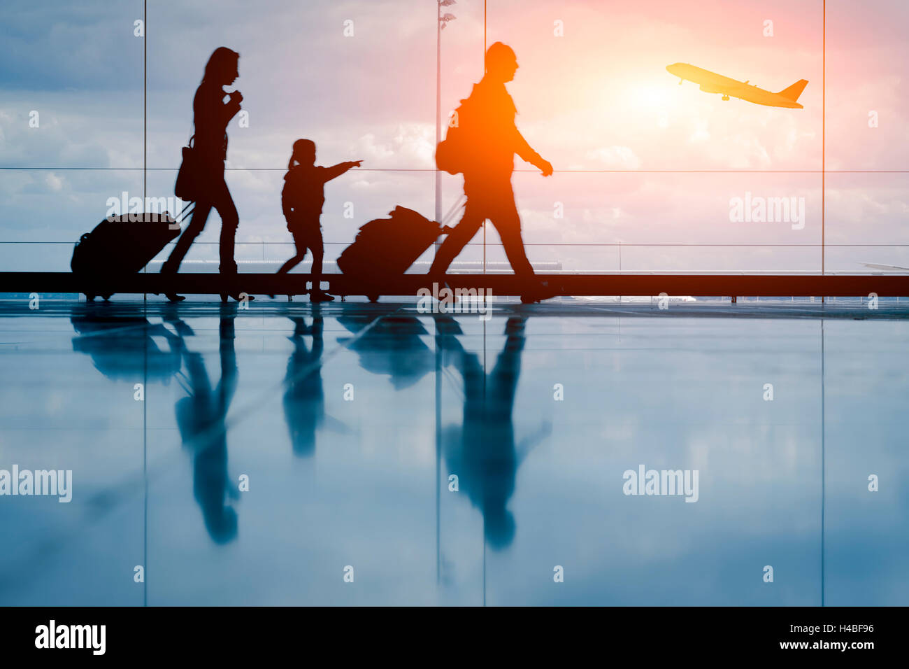 Silhouette of young family and airplane at airport - Stock Image