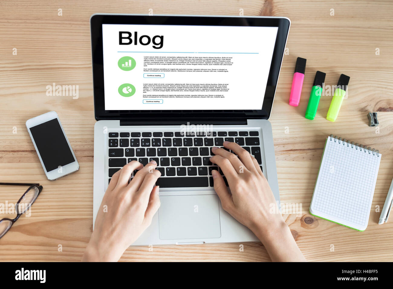 Woman blogging with laptop writing post entries - Stock Image