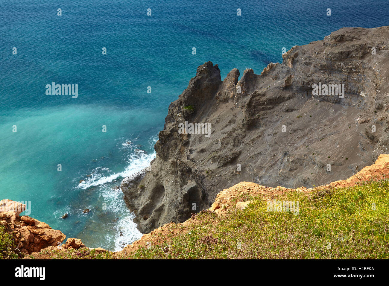 black basalt rock as a geologic anomaly at the rock coast at the Atlantic with Luz, west of Lagos, Algarve, Portugal, - Stock Image