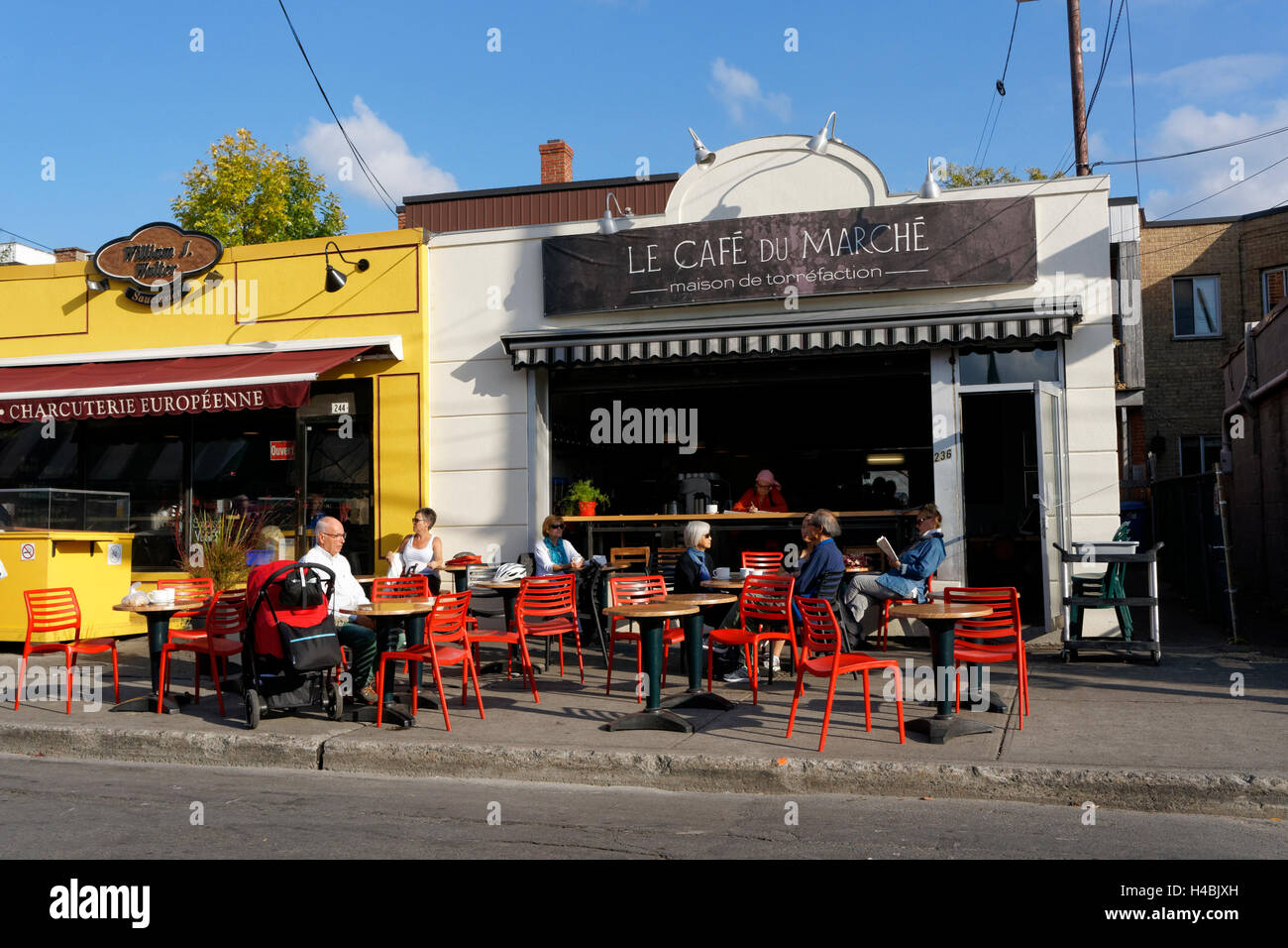 People sitting at tables outside the the Cafe de la Marche next to the Jean Talon Market, Montreal Quebec, Canada - Stock Image
