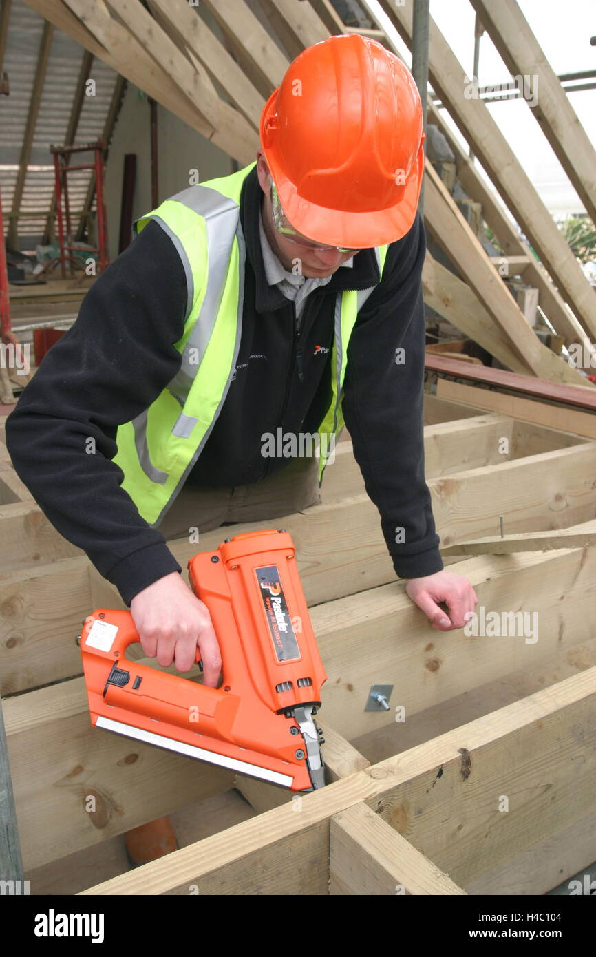 A builder uses a gas-powered nail gun to fix timber bracing between floor joists on a house undergoing refurbishment - Stock Image
