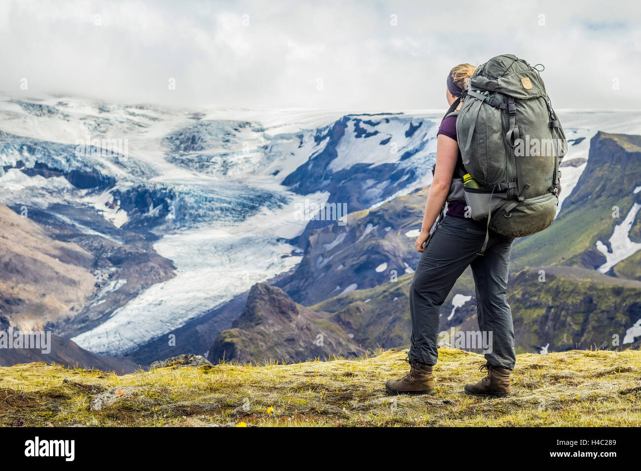 A young hiker overlooking a glacier in Thorsmörk - Stock Image