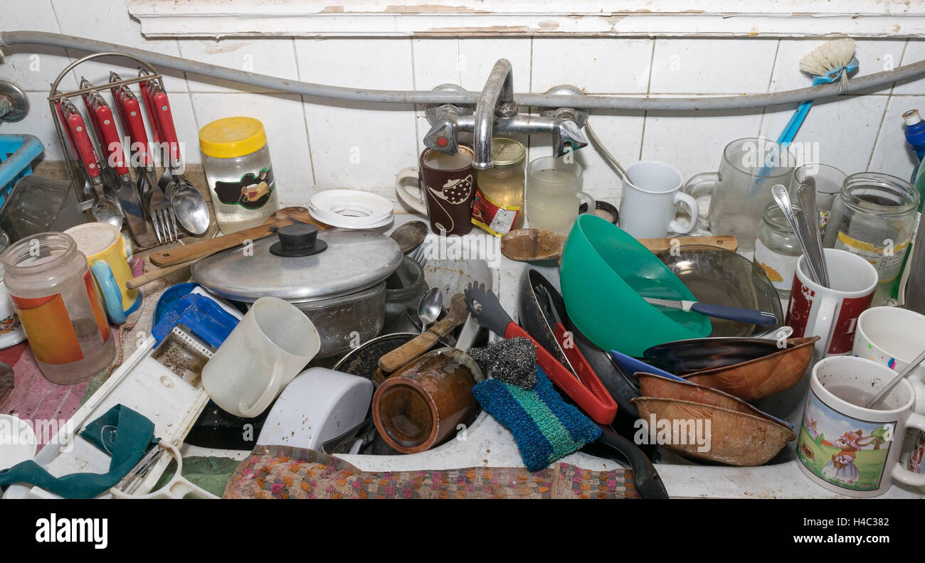Pile of dirty utensils in a kitchen washbasin - Stock Image
