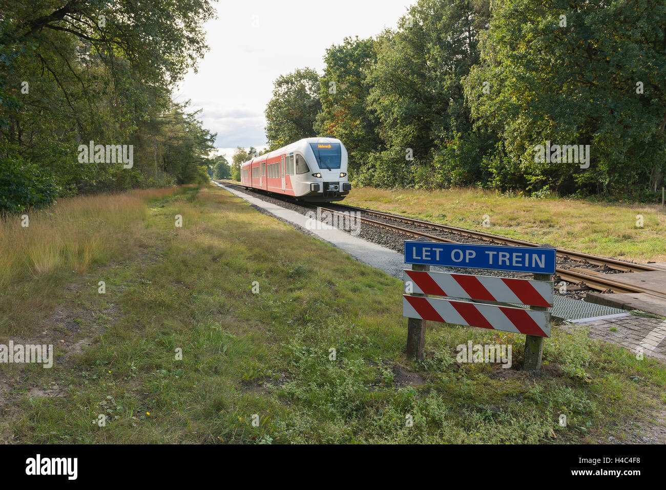 Passing diesel train with warning sign Please note train at a level crossing in the Achterhoek between Aalten and - Stock Image