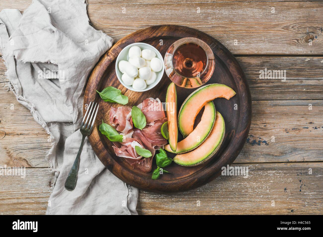 Prosciutto, melon, mozzarella and glass of wine in wooden tray - Stock Image