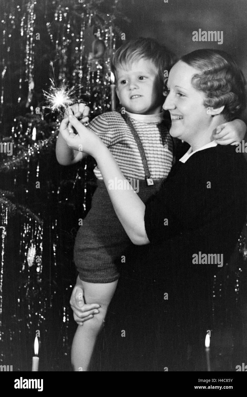 An Weihnachten freuen sich Mutter und Sohn an einer Wunderkerze, Deutschland 1930er Jahre. At christmas mother and Stock Photo