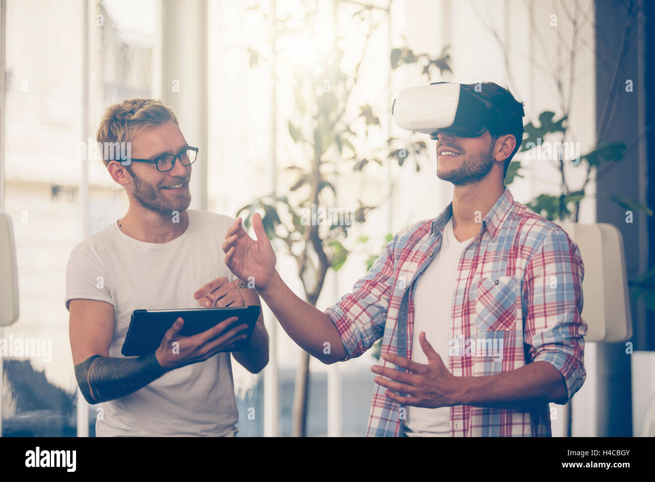 Entrepreneurs testing virtual reality technology with colleague in office. - Stock Image