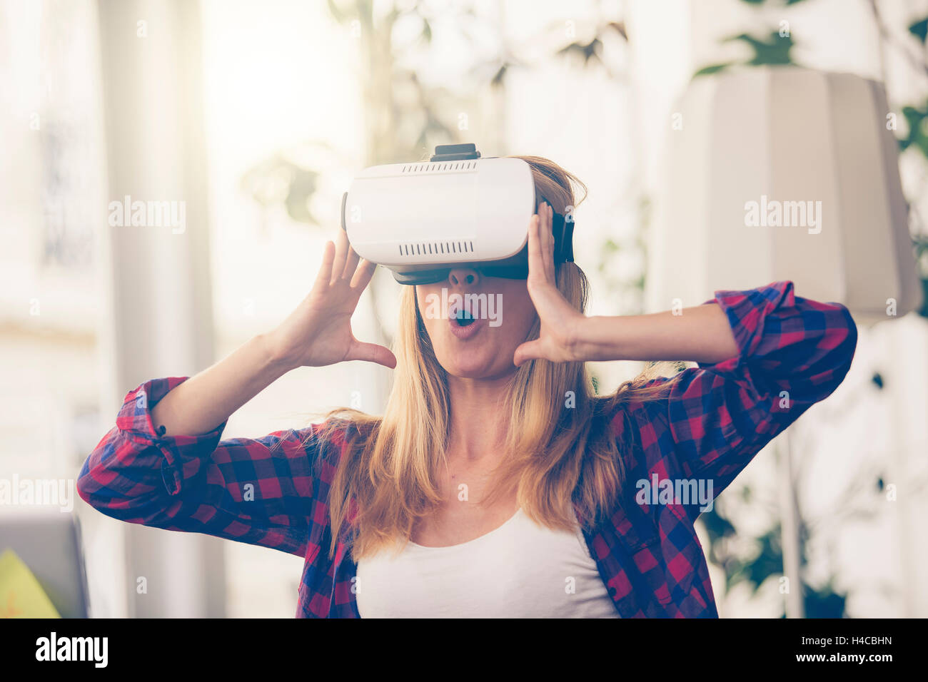 Amazed woman looking in a VR goggles and gesturing - Stock Image