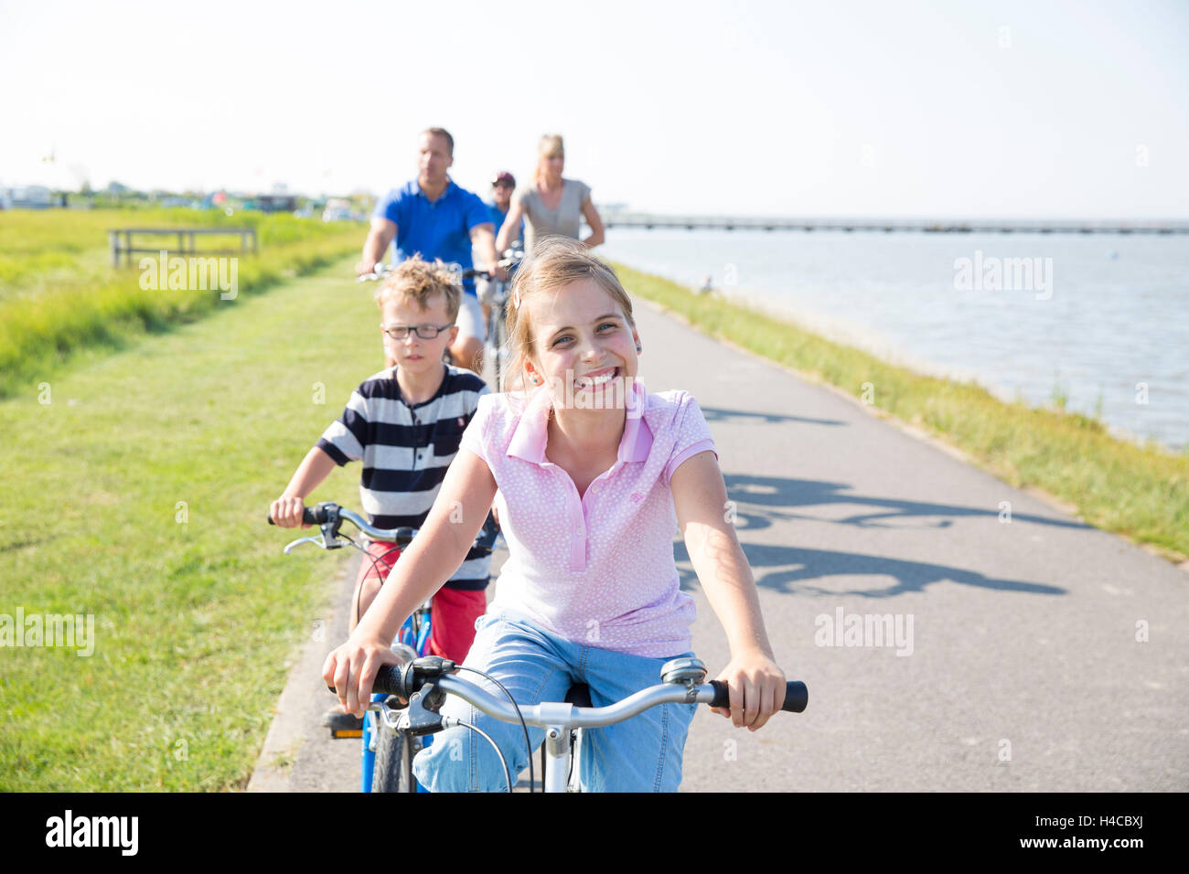 Family drives bicycle by the sea - Stock Image