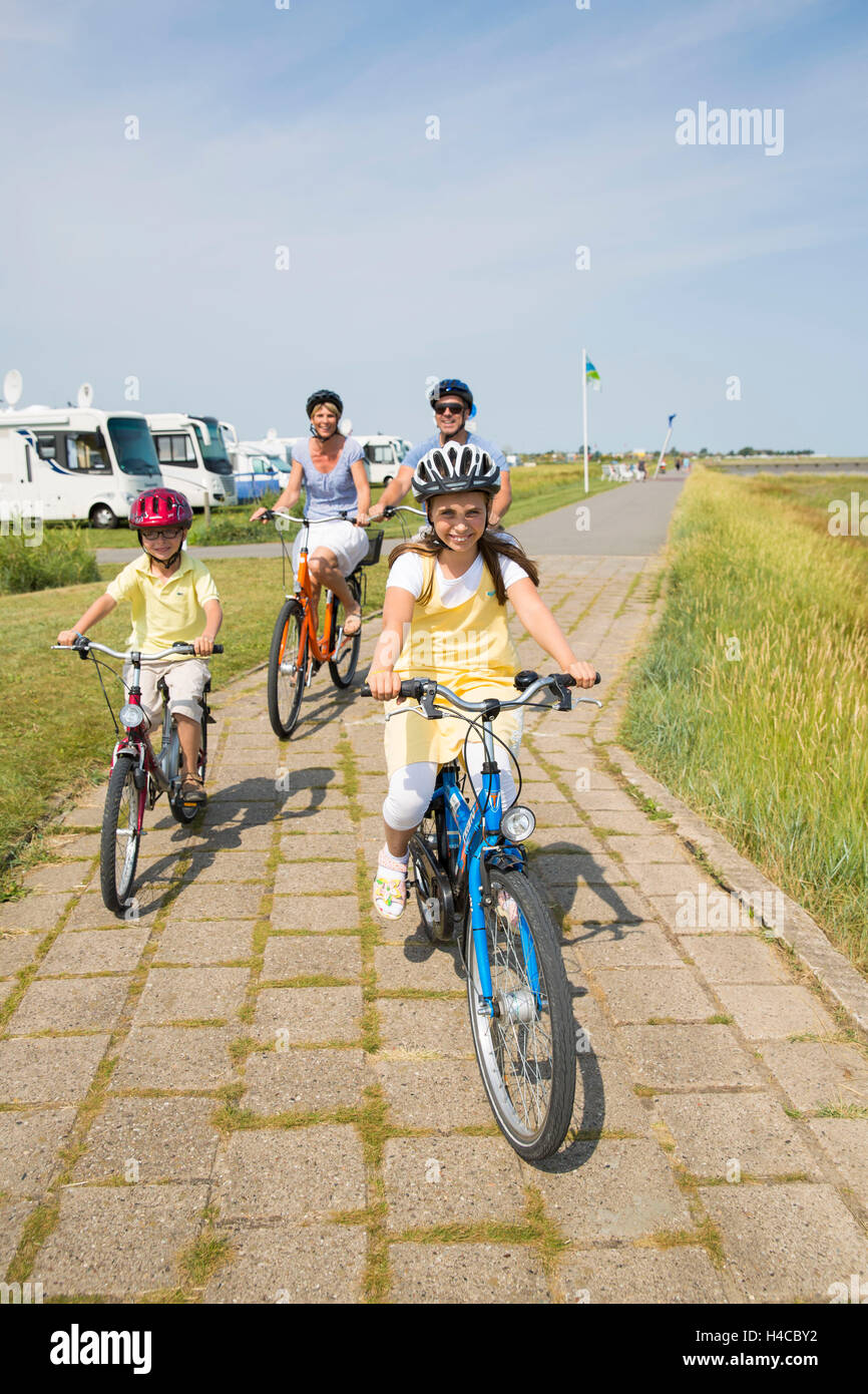 Family drives bicycle on the beach - Stock Image