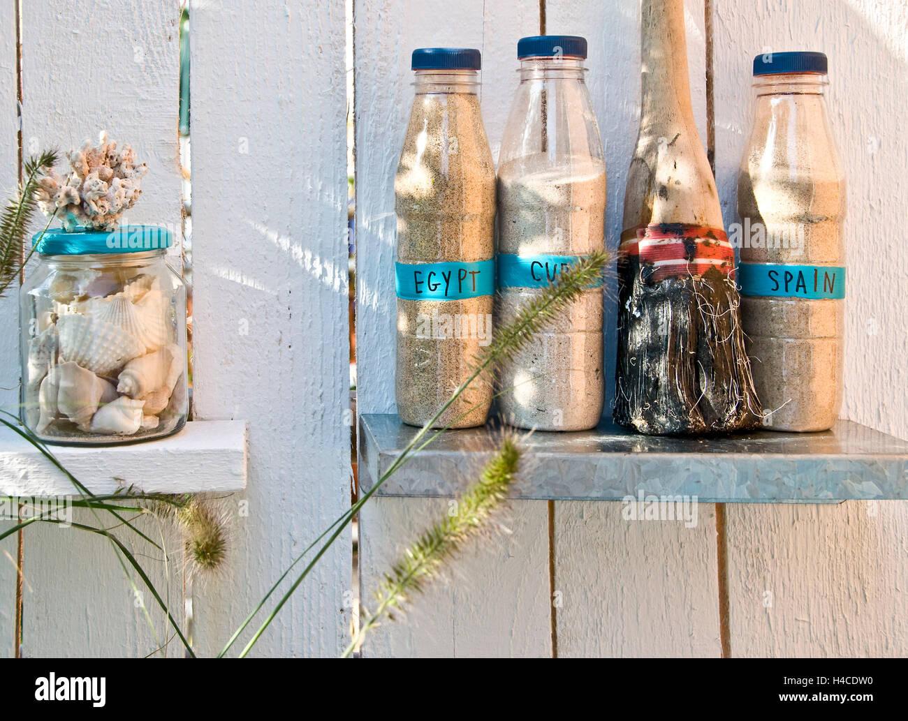 Shelves, bottles of Sand and flotsam and jetsam - Stock Image