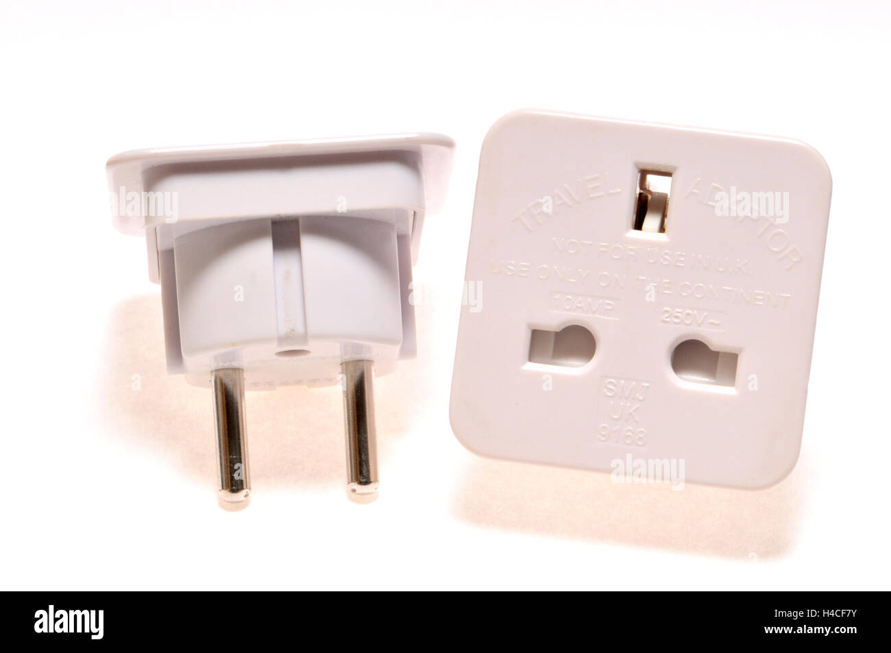 Travel plug adapter - for using a three pin UK plug in a two pin European socket - Stock Image