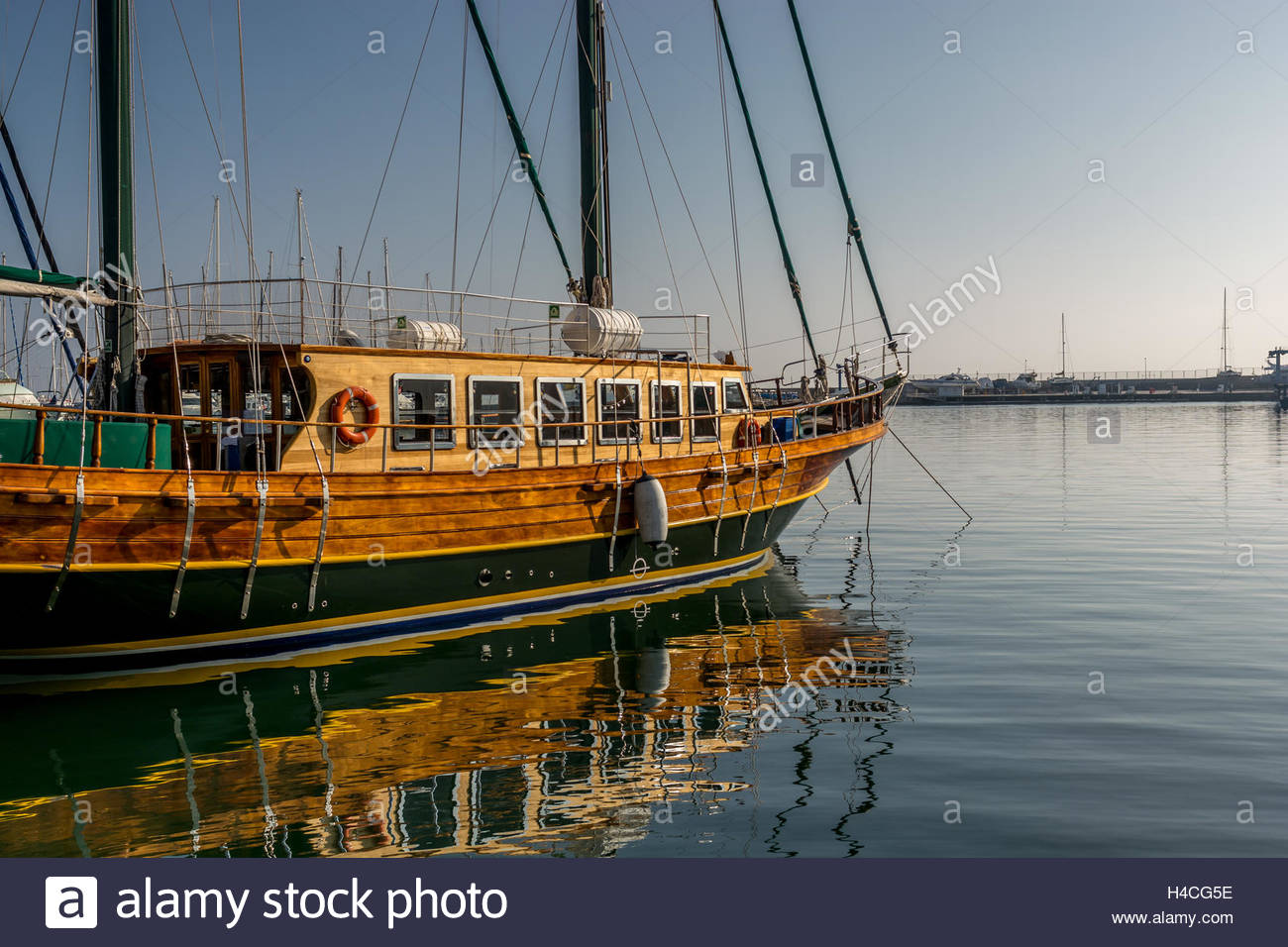Moored giant green wood  saling boat on  very calm sea just few minutes after sunrise. This is a common view in - Stock Image