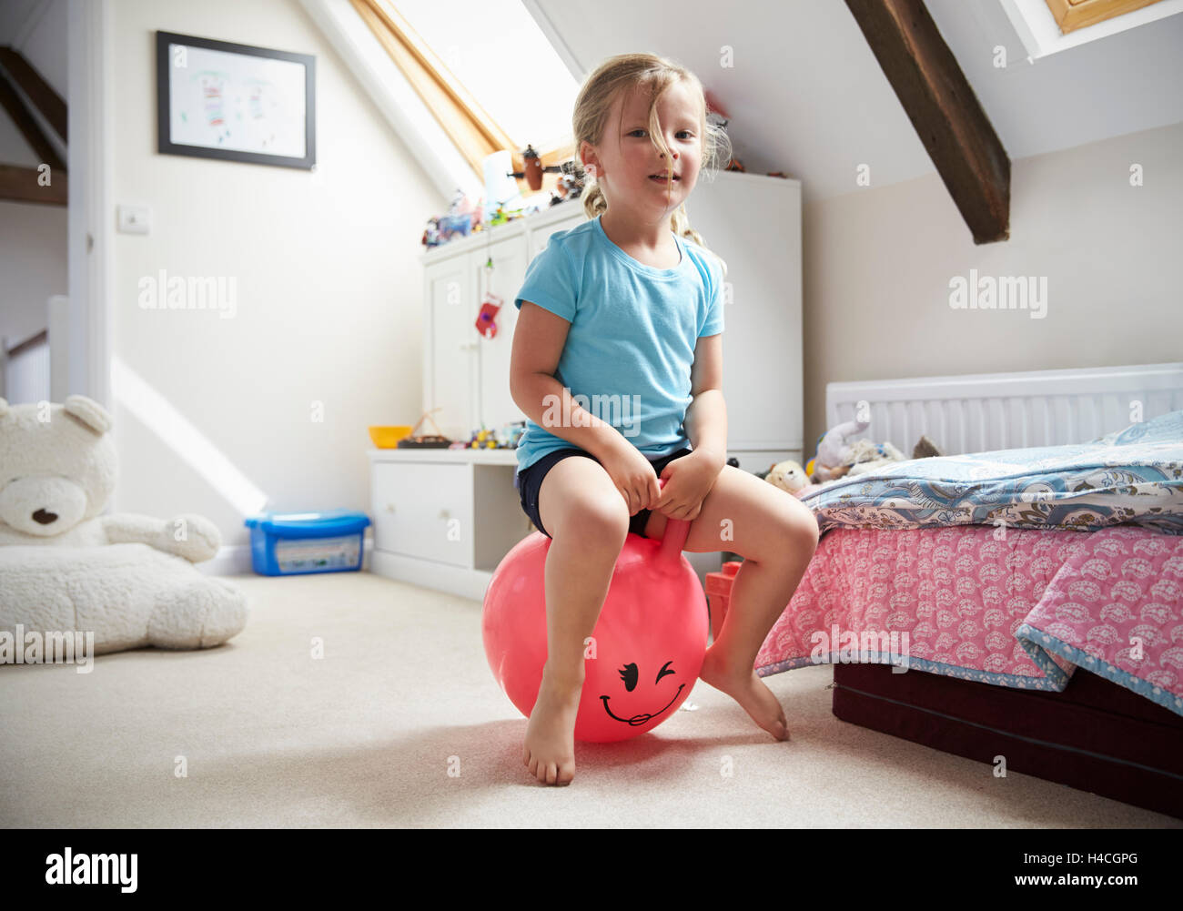 Girl Bounces On Inflatable Ball In Playroom - Stock Image