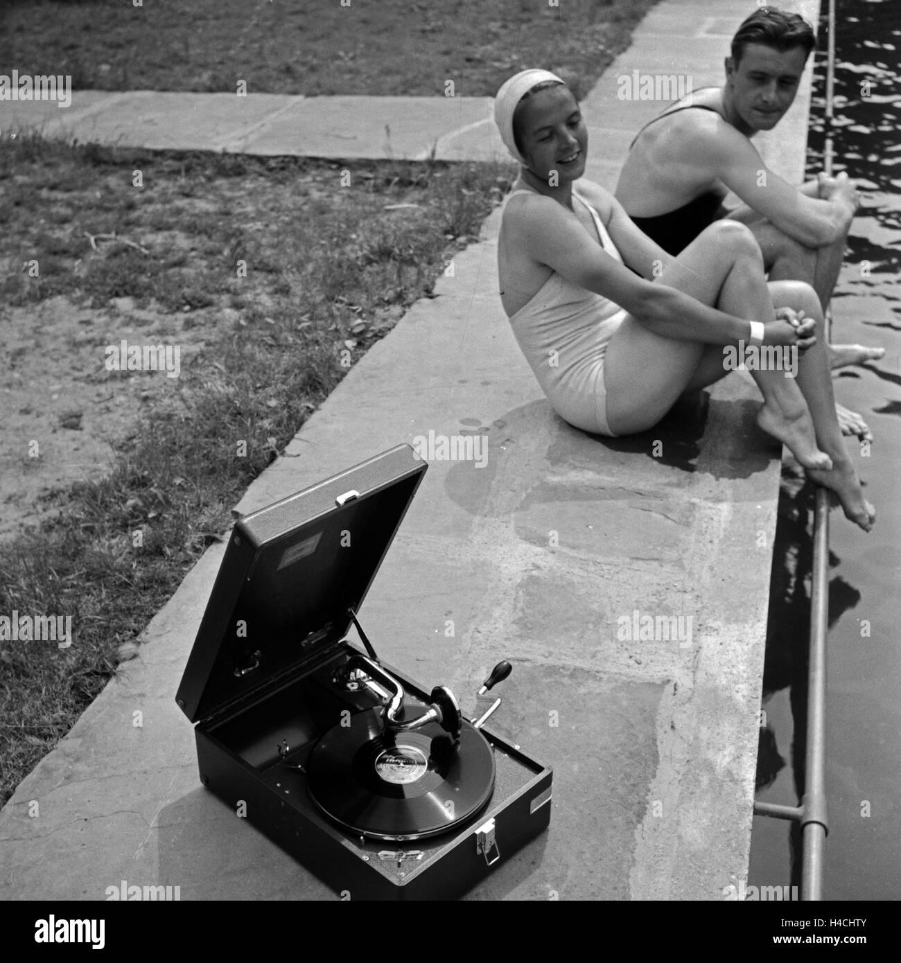 Ein junges Paar sitzt im Freibad am Beckenrand und hört die neuesten Schlager auf einem Elextrole Grammophon, - Stock Image