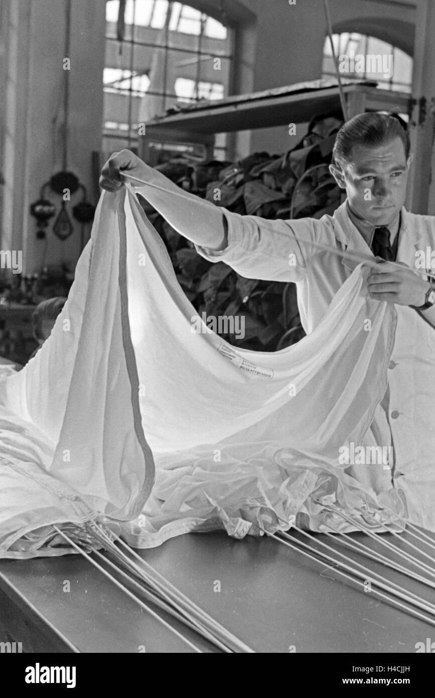 Anpassung des Gurtzeugs eines Fallschirms in einer Fallschirm Näherei, Deutschland 1940er Jahre. Checking the harness Stock Photo