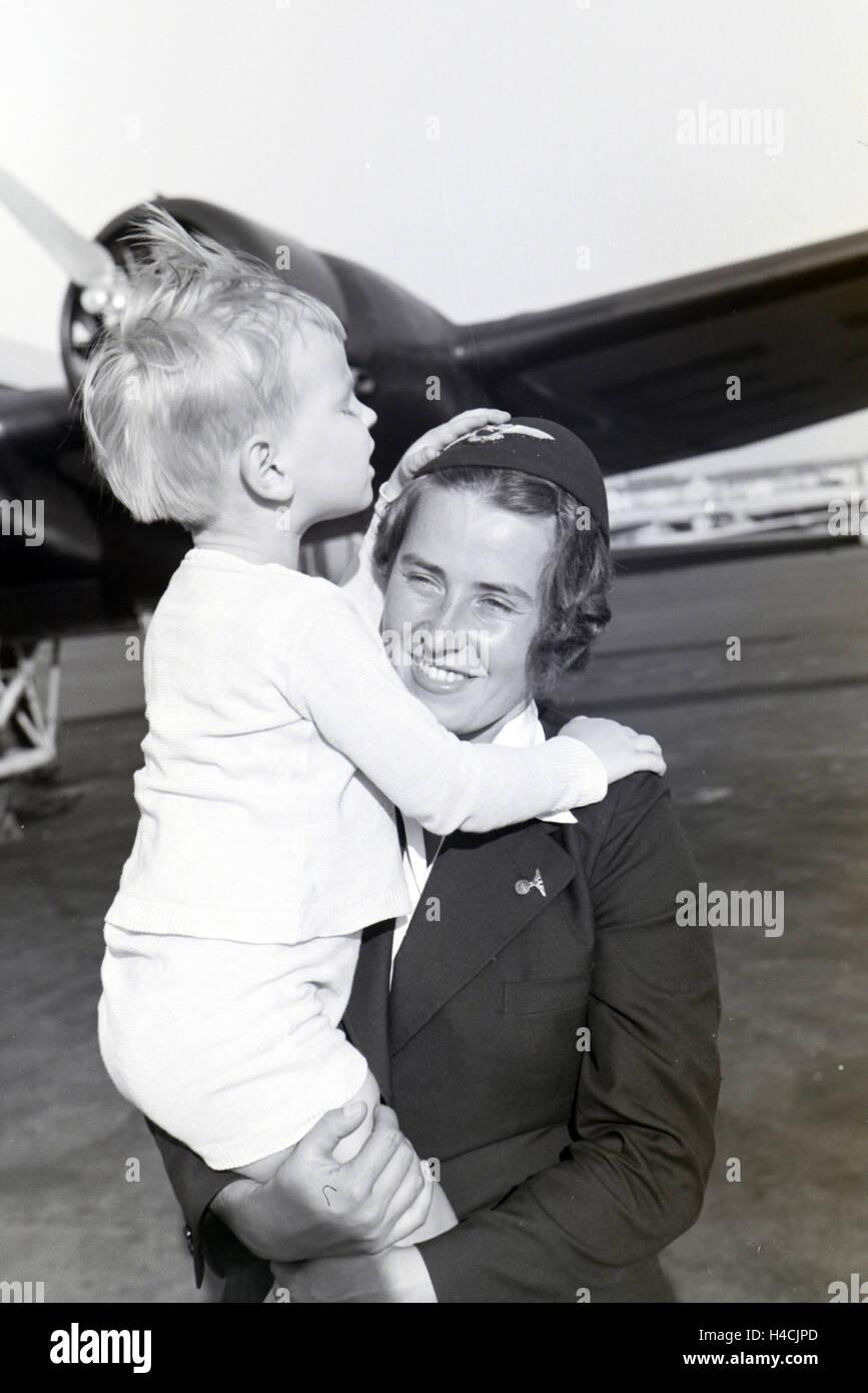 Stewardess trgt kleinen Jungen auf den Armen ber das Flugfeld, Deutschland 1930er Jahre. Stewardess carrying a little - Stock Image