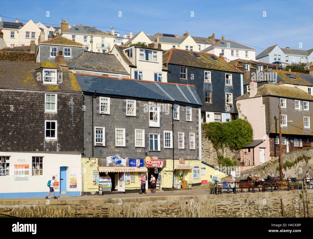 Quayside with shops and houses above the harbour, Mevagissey, Cornwall, England, UK - Stock Image