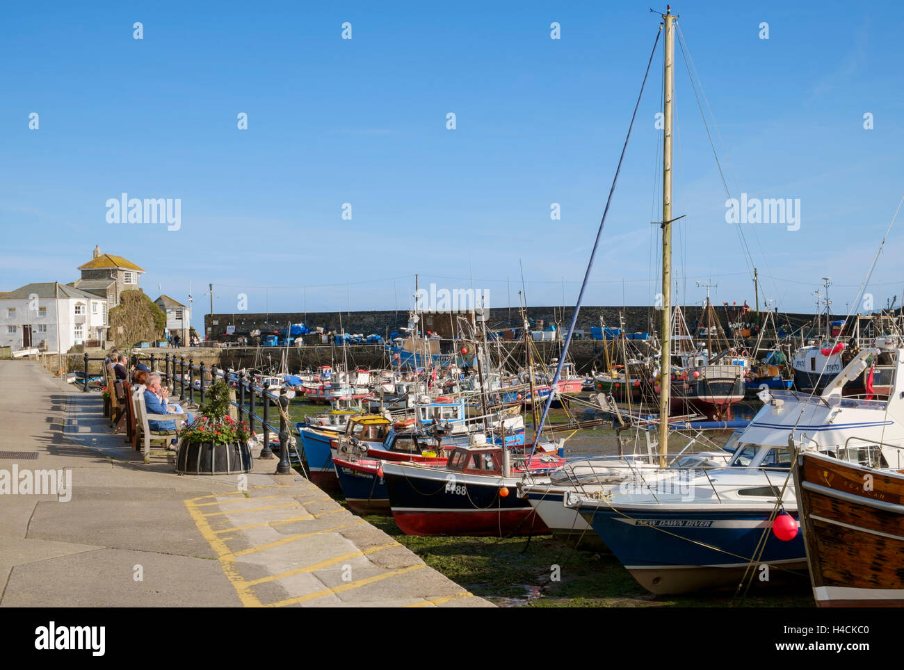 Tourists on the quayside at Mevagissey harbour & fishing port, Cornwall, England, UK - Stock Image