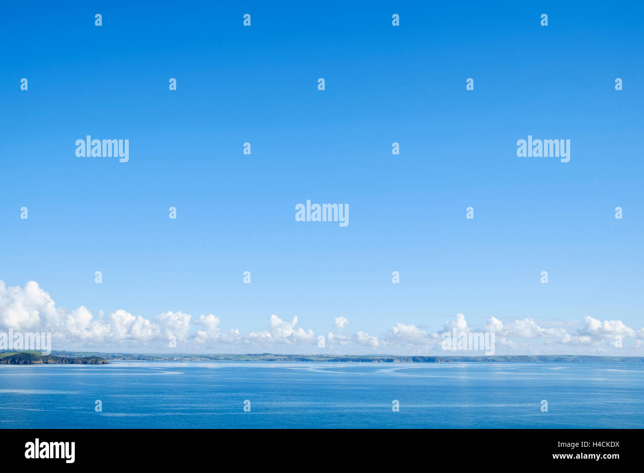 Weather - Blue sky with Cumulus clouds forming over a coastline, UK - Stock Image