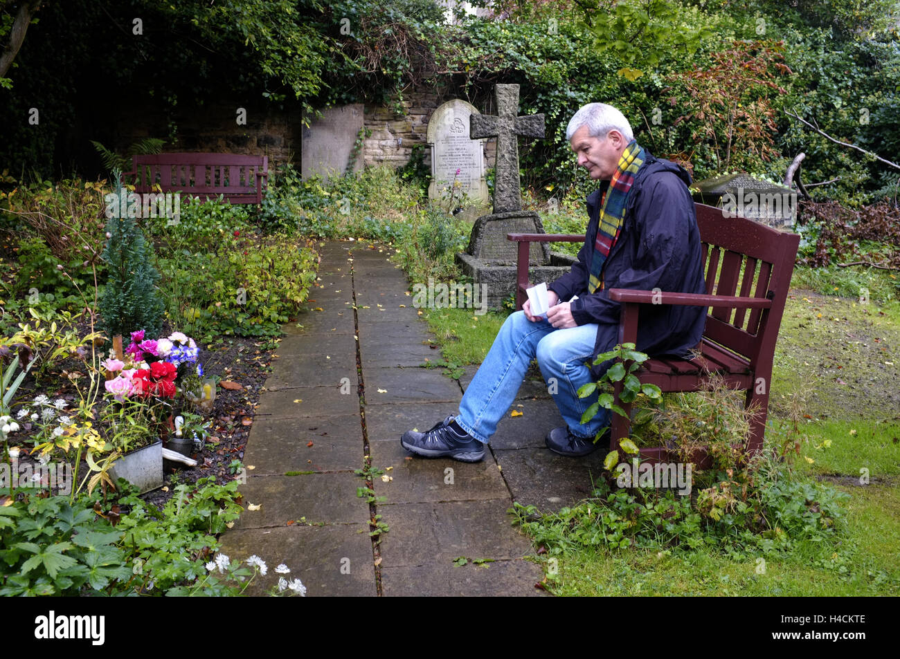 Man Grieving at Graveside - Stock Image